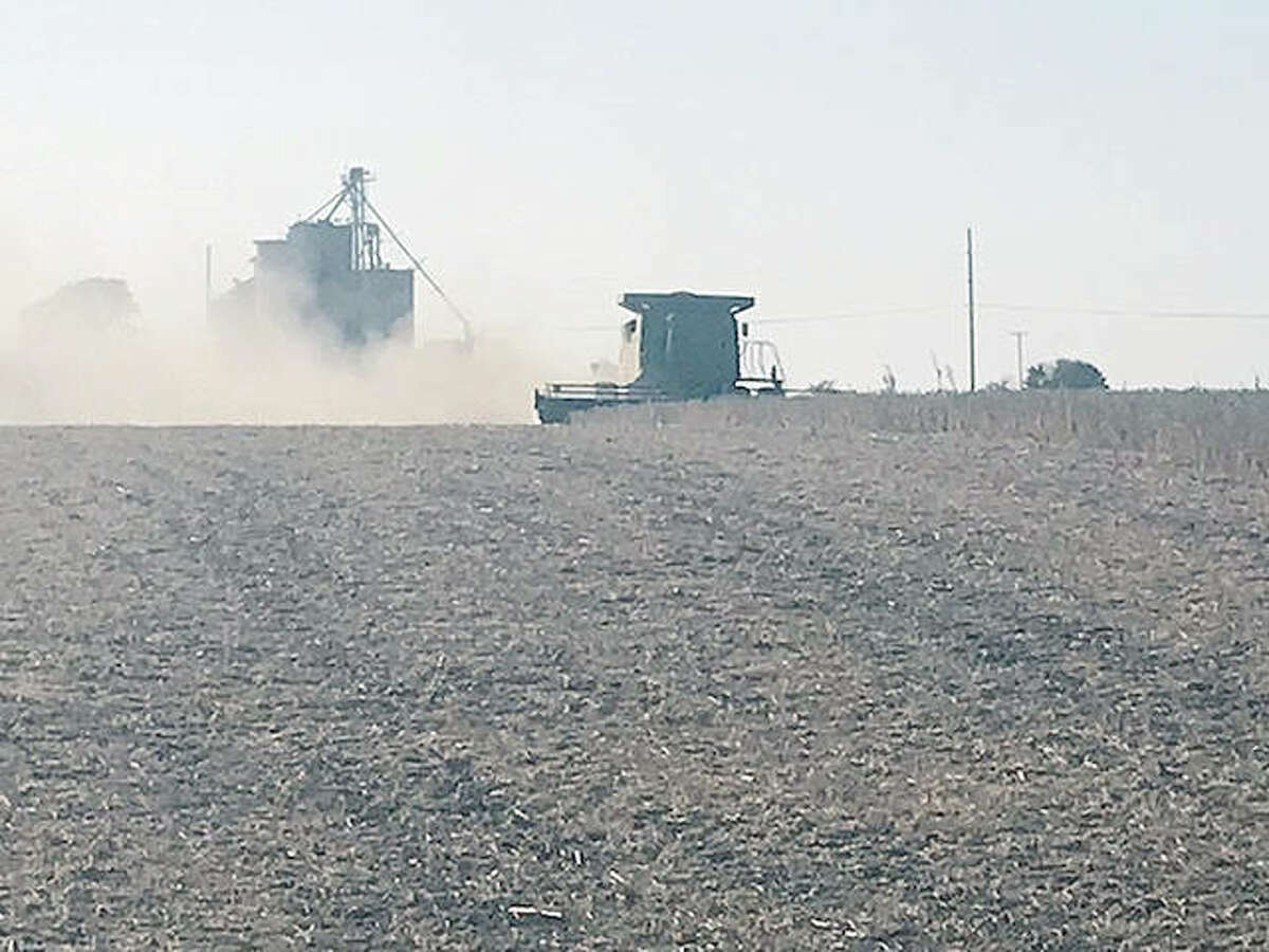 Dust rises from the soil as a farmer near New Berlin wraps up soybean harvesting for the season.