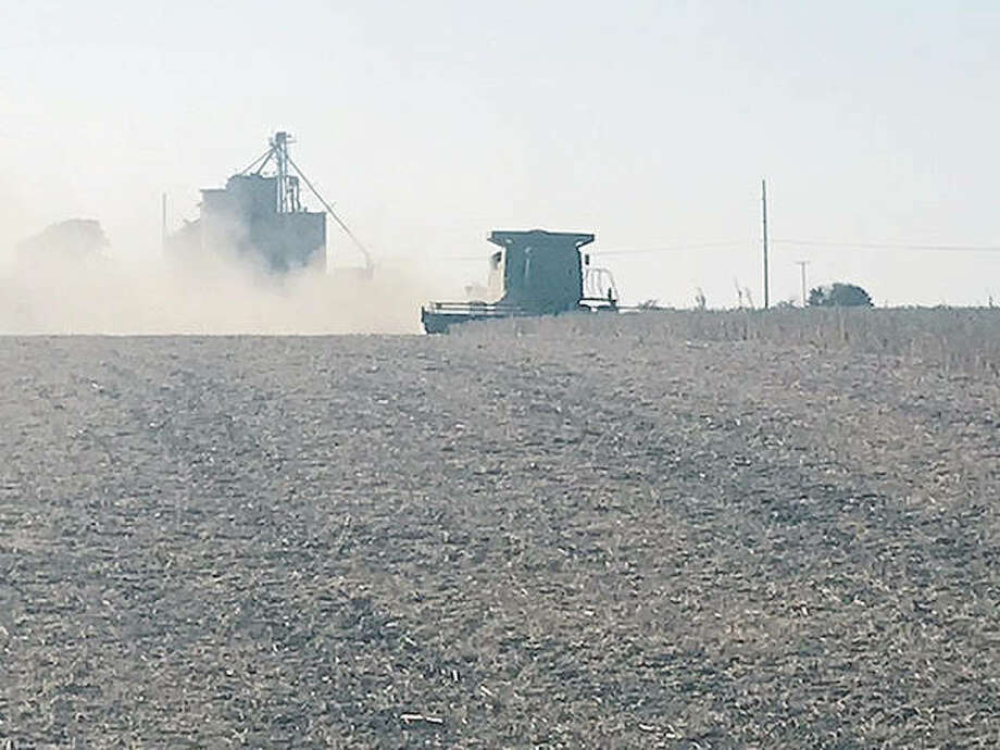 Dust rises from the soil as a farmer near New Berlin wraps up soybean harvesting for the season. Photo: Bob Fromme   Reader Photo
