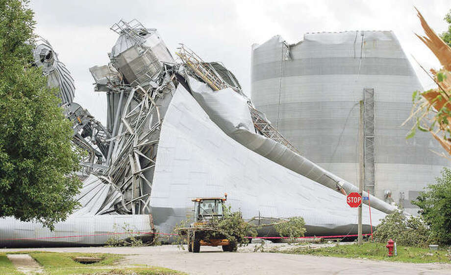 Workers help with tree debris removal as grain bins from the Archer Daniels Midland facility are seen severely damaged in Keystone, Iowa, on Aug. 12. Damage estimates from a rare wind storm that slammed Iowa and some other parts of the Midwest in August are growing, with the total now at $7.5 billion, according to a new report. Photo: Jim Slosiarek   The Gazette (AP)