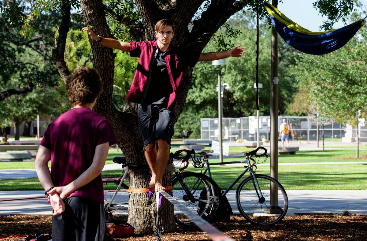 Patrick Quinn, 19, walks on a slack line while hanging out with friends at the Texas A&M campus Friday, Oct. 2, 2020, in College Station, Texas.