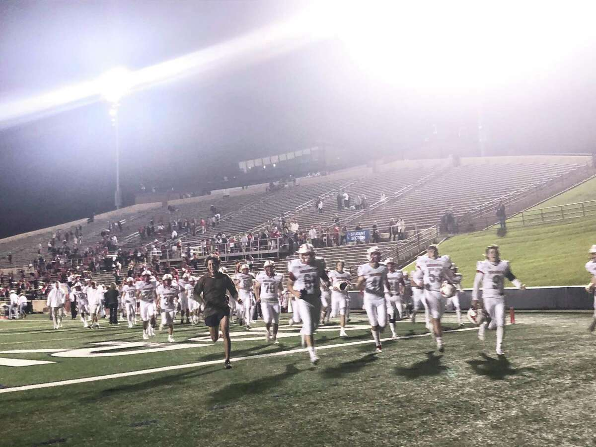 The Memorial Mustangs run off the field following their 41-0 victory over the Spring Woods Tigers at Tully Stadium on Oct. 16