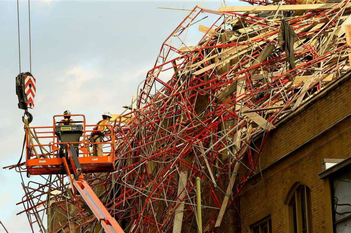 Workers attempt to remove the collapsed scaffolding from the parish hall next to St. Mark's Episcopal Church on Sept. 21, 2019.