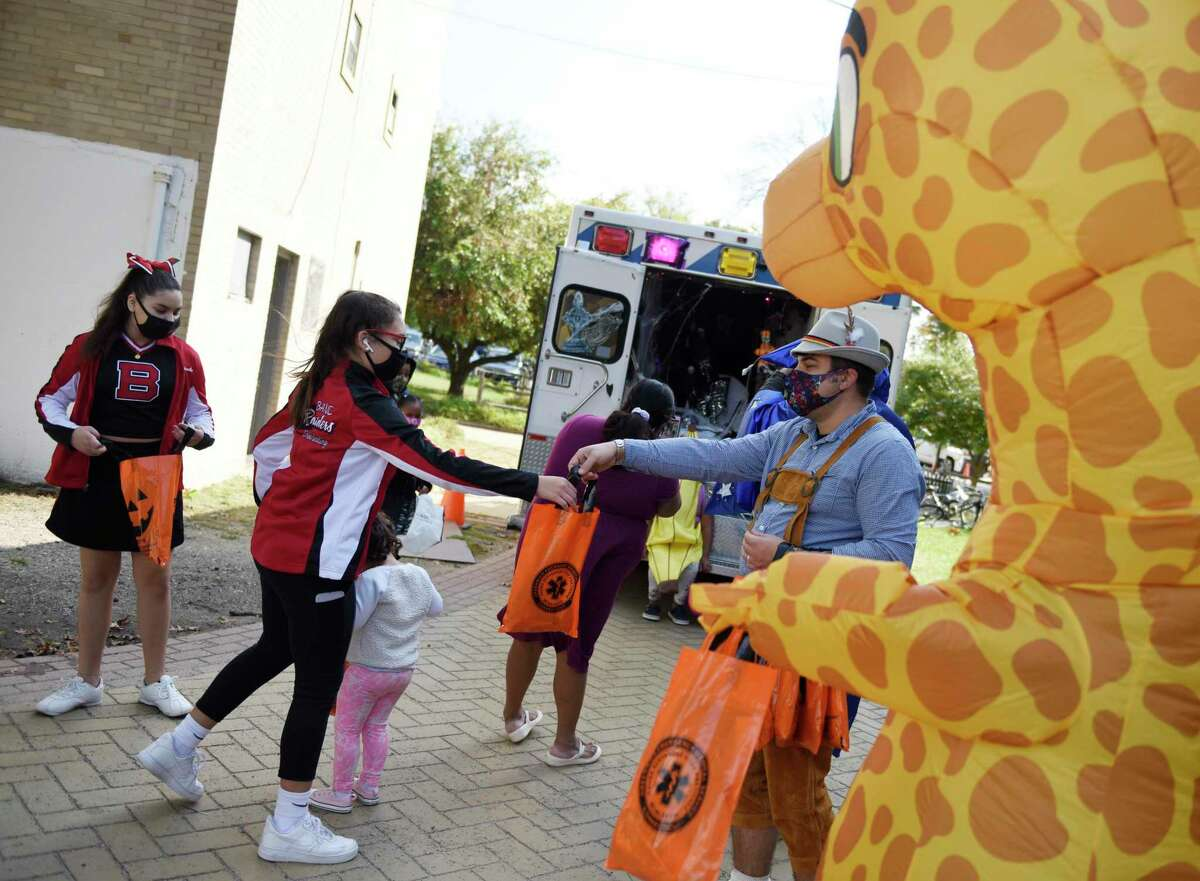 Dressed as cheerleaders, Micala Bustelo, left, 11, and Sophia Villar, 12, get candy at the Greenwich EMS trick-or-treat kids' Halloween event at Armstrong Court in the Chickahominy section of in Greenwich, Conn. Sunday, Oct. 18, 2020. GEMS visited Armstrong Court, Wilbur Peck, and Adams Garden public housing complexes with a spooky ambulance and people dressed in costumes to give away candy to children.