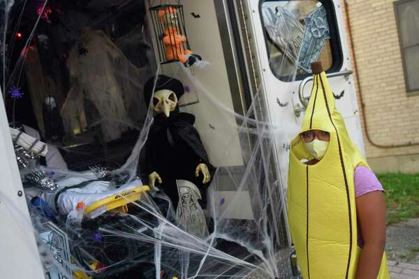 Dressed as a banana, Haylli Chavoya, 9, peeks inside the skoopy ambulance at the Greenwich EMS trick-or-treat kids' Halloween event at Armstrong Court in the Chickahominy section of in Greenwich, Conn. Sunday, Oct. 18, 2020. GEMS visited Armstrong Court, Wilbur Peck, and Adams Garden public housing complexes with a spooky ambulance and people dressed in costumes to give away candy to children.