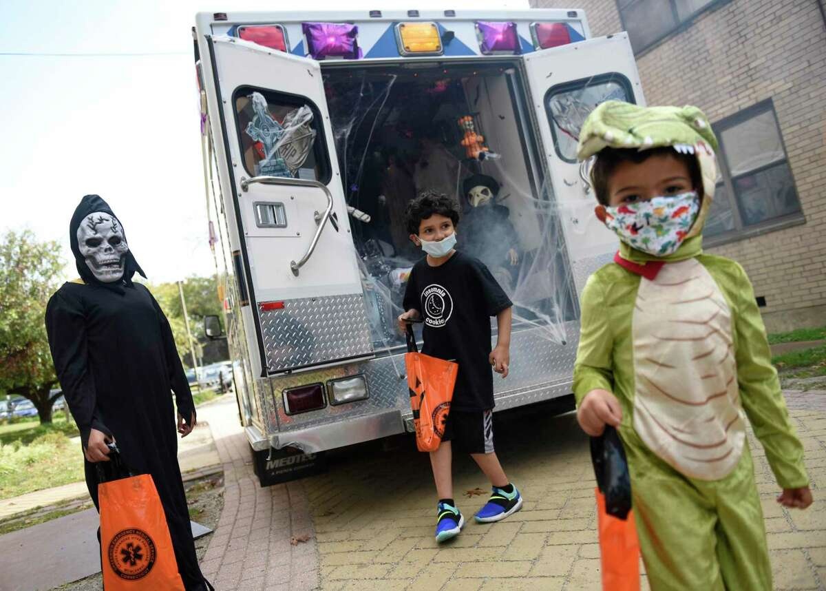 Children are dressed in costumes at the Greenwich EMS trick-or-treat kids' Halloween event at Armstrong Court in the Chickahominy section of in Greenwich, Conn. Sunday, Oct. 18, 2020. GEMS visited Armstrong Court, Wilbur Peck, and Adams Garden public housing complexes with a spooky ambulance and people dressed in costumes to give away candy to children.