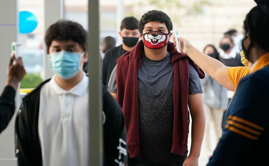 Enrique Alpizar, 16, a junior, right, has his temperature taken as he and other students return for the first day of in-person classes at Booker T. Washington High School, Washington High School 4204 Yale St., Monday, October 19, 2020 in Houston. Photo: Melissa Phillip/Houston Chronicle