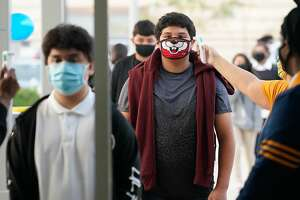 Enrique Alpizar, 16, a junior, right, has his temperature taken as he and other students return for the first day of in-person classes at Booker T. Washington High School, Washington High School 4204 Yale St., Monday, October 19, 2020 in Houston.