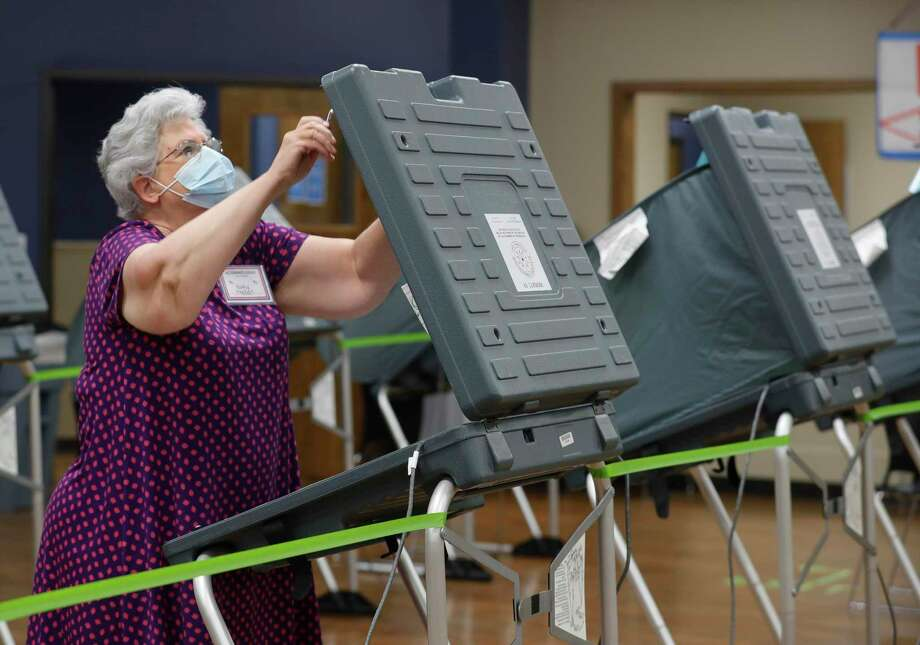 Montgomery County commissioners approved opening two new polling locations during a special meeting Monday morning as voter turnout has remained high, surpassing 2016 totals by just over 4,100 in the first five days of early voting. In this file photo, Kathy Trahan wears a facemask as she sets up voting stations before the polls open at the South Montgomery County Community Center in The Woodlands. Photo: Jason Fochtman, Houston Chronicle / Staff Photographer / 2020 © Houston Chronicle