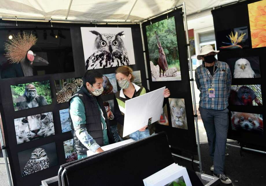 Stamford's Philip Schweiger and Katie Haas browse photos from Bruce Franklin's Fine Art Kingdom booth at the Stamford Downtown Arts & Crafts on Bedford Street event in Stamford, Conn. Sunday, Oct. 18, 2020. The arts and crafts show and sale returned for a second time as Bedford Street closed down to traffic to allow folks to browse more than 20 stands and enjoy outdoor dining with extended outdoor patio cafes. Local and regional vendors displayed a variety of work including paintings, photography, sculpture, candles, garments, jewelry, hats and gloves, and much more. Photo: Tyler Sizemore / Hearst Connecticut Media / Greenwich Time