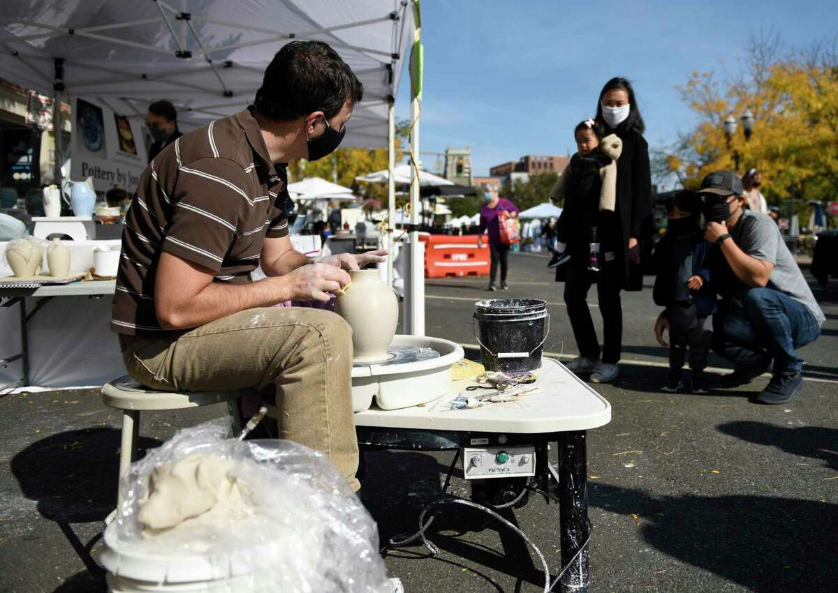 John Puzzuoli creates a vase beside his pottery booth at the Stamford Downtown Arts & Crafts on Bedford Street event in Stamford, Conn. Sunday, Oct. 18, 2020. The arts and crafts show and sale returned for a second time as Bedford Street closed down to traffic to allow folks to browse more than 20 stands and enjoy outdoor dining with extended outdoor patio cafes. Local and regional vendors displayed a variety of work including paintings, photography, sculpture, candles, garments, jewelry, hats and gloves, and much more.