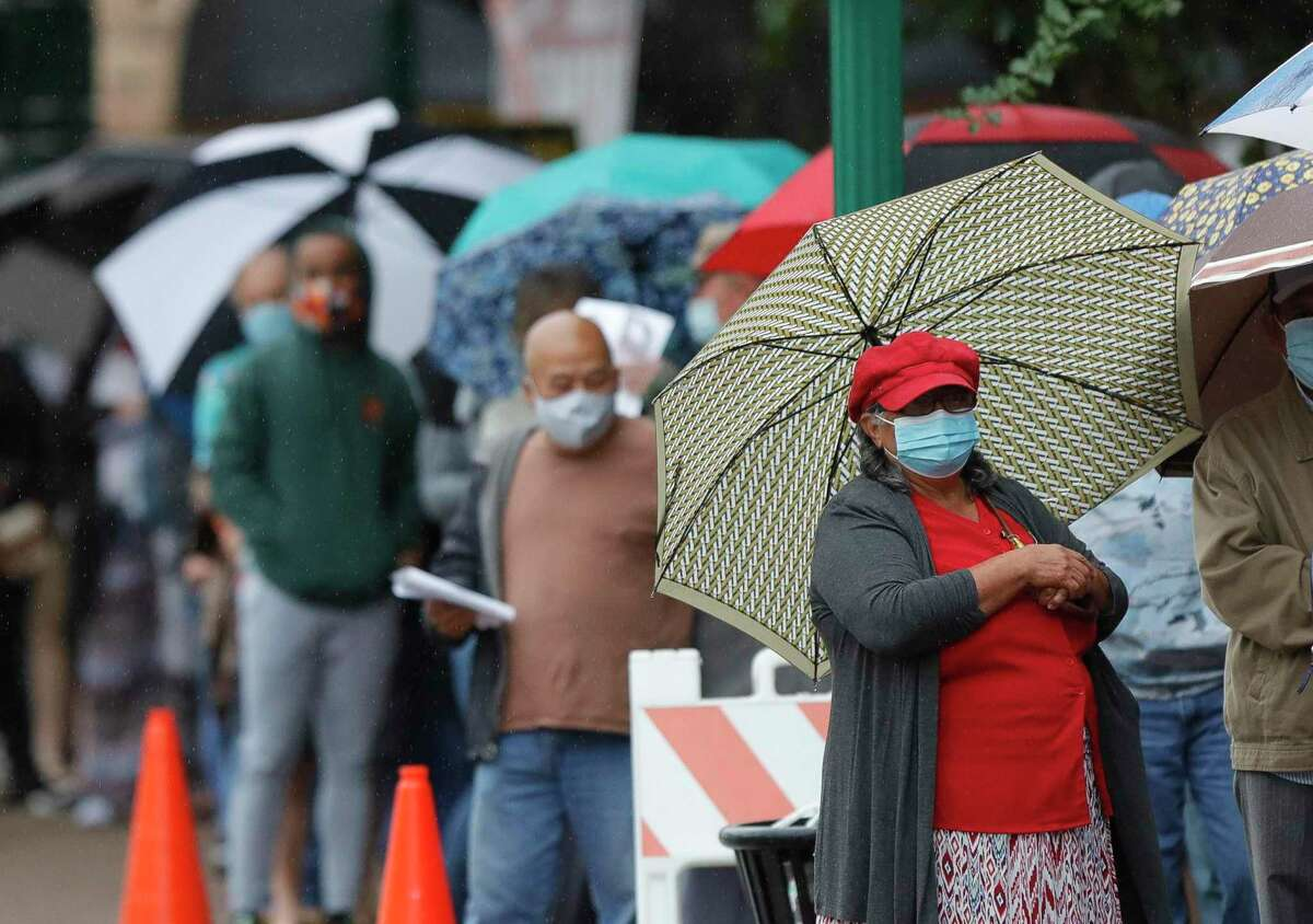Residents bundle up in 50 degree, rainy weather to vote at the Lee G. Alworth Building after a cool front moved through Montgomery County, Friday, Oct. 16, 2020, in Conroe.