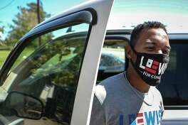Rashad Lewis, the Democratic candidate for Texas' 36th Congressional District, dons a Lewis For Congress mask as he gets out of his truck Wednesday, Sept. 30, 2020 in Jasper, Texas. Lewis, 34, a lumberjack by trade, ran an insurgent write-in campaign to become the youngest person ever to serve on the Jasper City Council at the age of 30. This fall, he's reaching significantly higher, challenging entrenched incumbent Rep. Brian Babin in Congressional District 36. In a Republican-dominated region, he is the first person of color to run for the seat.
