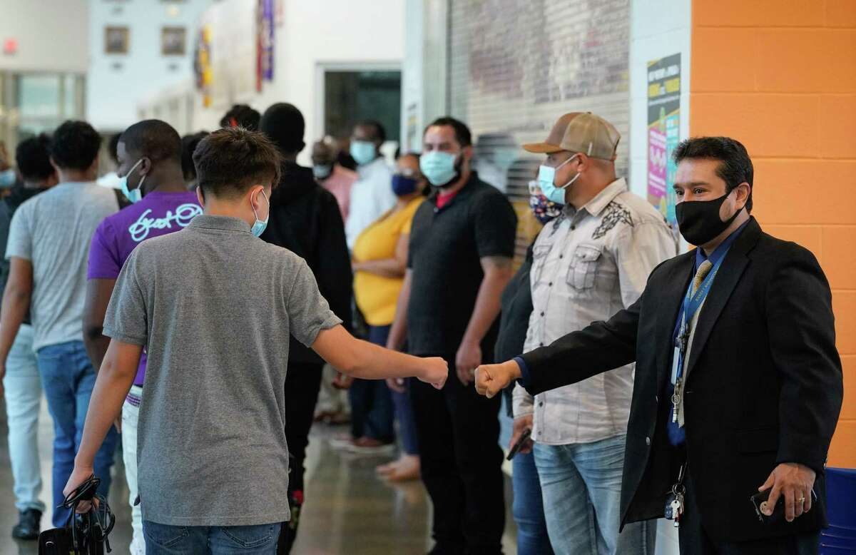 Booker T. Washington High School staff member Francisco Rivera, right, gives a fist bump as students returning for the first day of in-person classes at the Houston ISD campus Monday.
