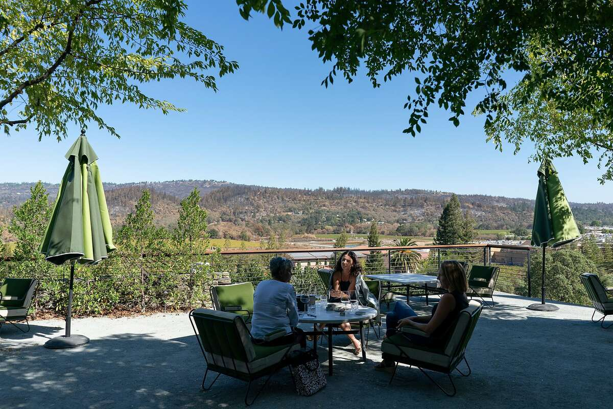 Kim Elwell, Jen Beloz, and Kim Westerman wine taste on the outdoor terrance of the Faust Haus in St. Helena, California.