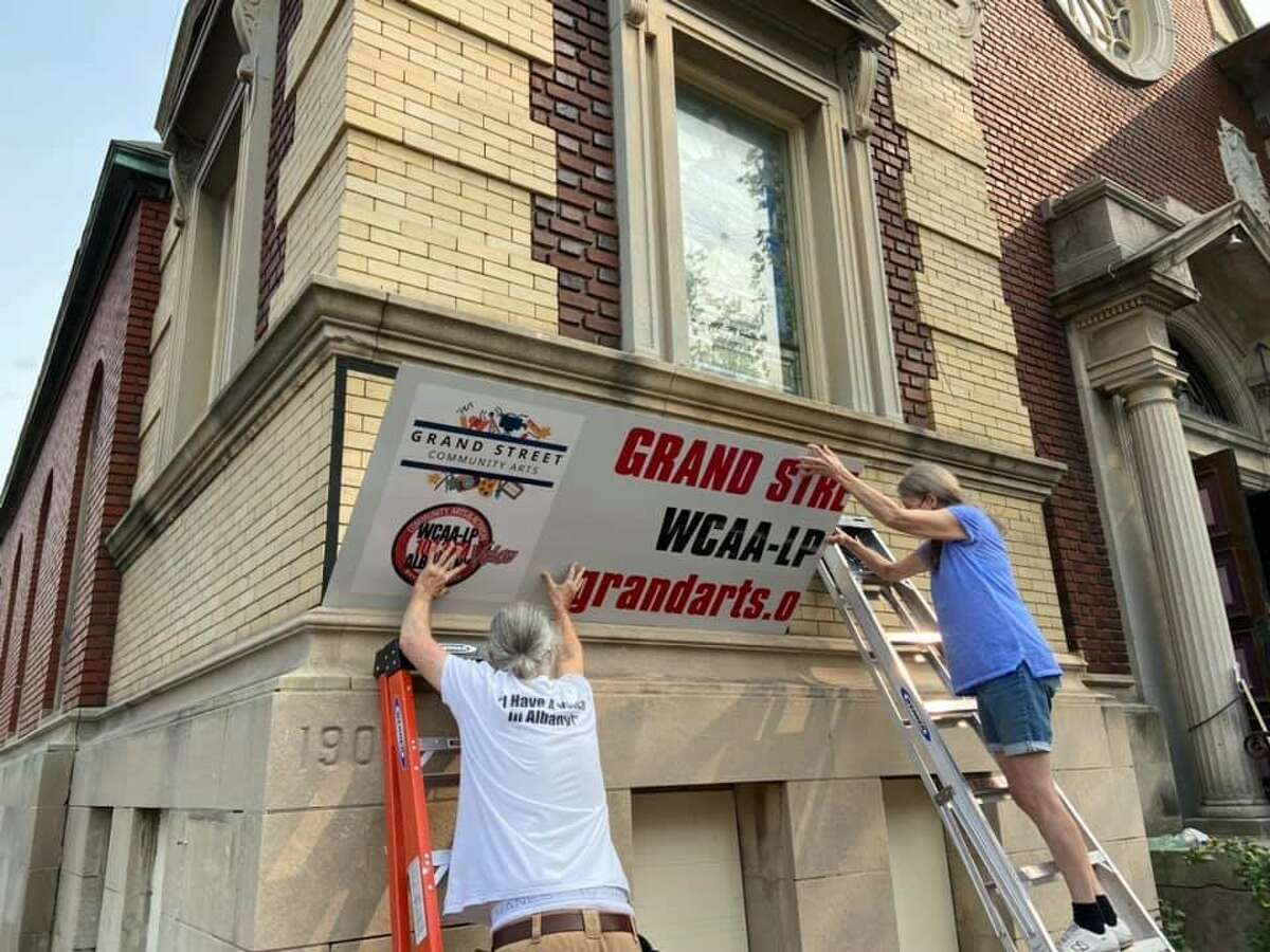 The raising of the Grand Street Community Arts sign.