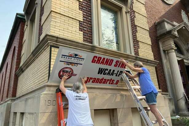 The raising of the Grand Street Community Arts sign.