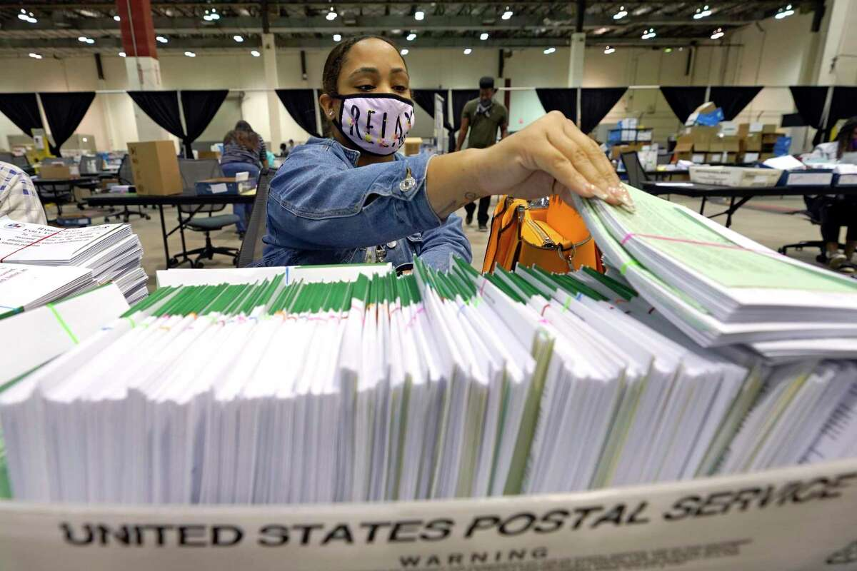Harris County election worker Romanique Tillman prepares mail-in ballots to be sent out to voters Tuesday, Sept. 29, 2020, in Houston. (AP Photo/David J. Phillip)