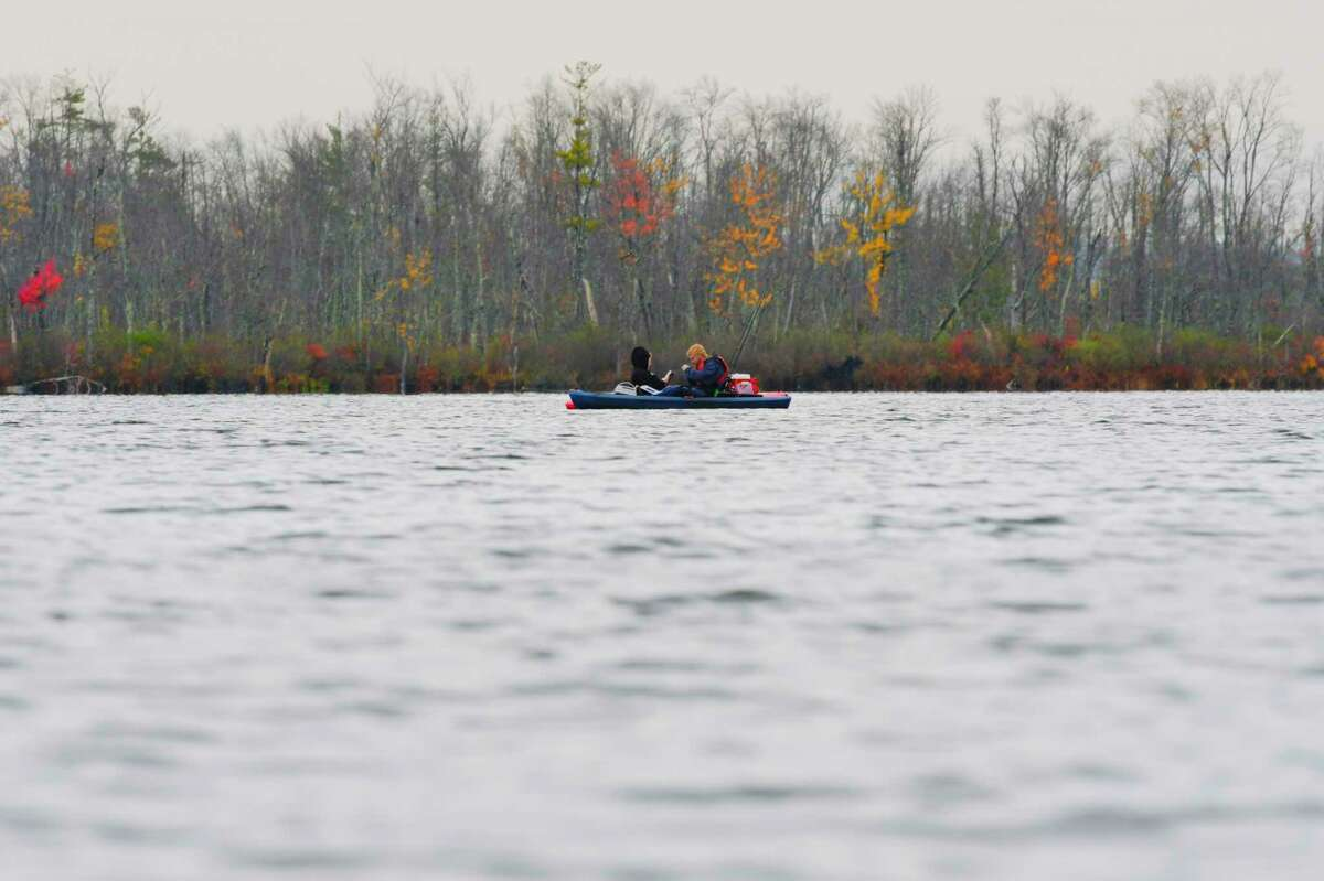 A woman reads a book in her kayak as a man fishes from his on Ballston Lake on Monday, Oct. 19, 2020, in Ballston Lake, N.Y. (Paul Buckowski/Times Union)