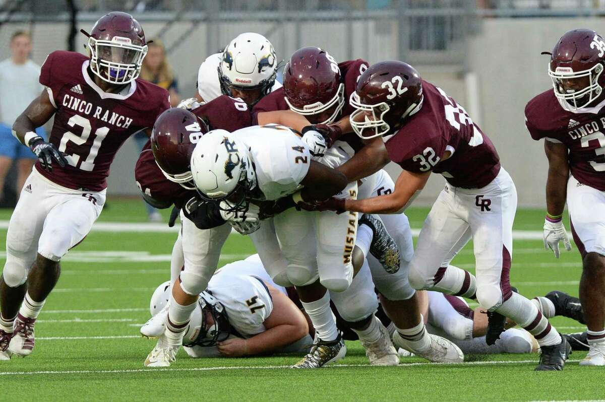 A trio of Cinco Ranch defenders tackle Kameron Burton (24) of Cy Ranch in the first quarter of a high school football game between the Cinco Ranch Cougars and the Cy Ranch Mustangs on Saturday, August 31, 2019 at Legacy Stadium, Katy, TX.