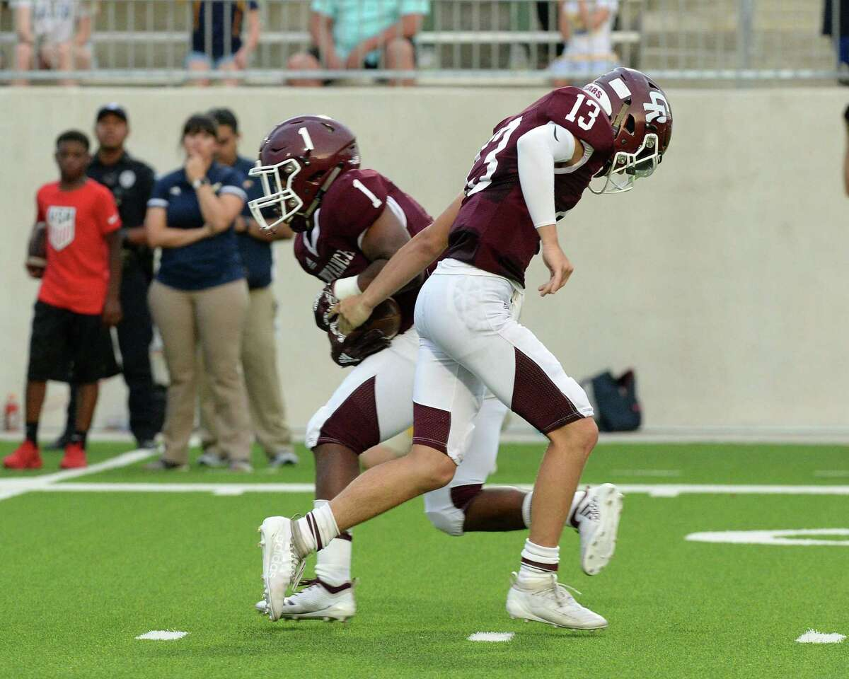 Caleb Leapheart (1) of Cinco Ranch takes a handoff from Evan Dunn (13) in the first quarter of a high school football game between the Cinco Ranch Cougars and the Cy Ranch Mustangs on Saturday, August 31, 2019 at Legacy Stadium, Katy, TX.