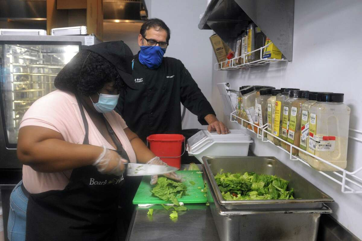 Cassie, a student at Boys & Girls Village, works to prepare salads in the cafeteria on the village's campus in Milford. She is seen here with life skills and vocational culinary instructor Bill Weitzler.