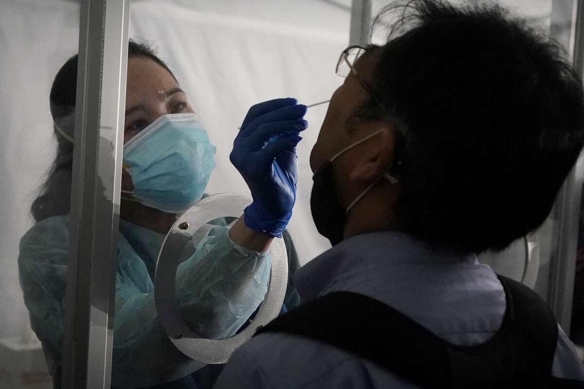 A reporter, right, gets a rapid COVID-19 test from June Lopez, Dignity GoHealth medical assistant, during a demonstration at San Francisco International Airport in San Francisco, Thursday, Oct. 15, 2020.