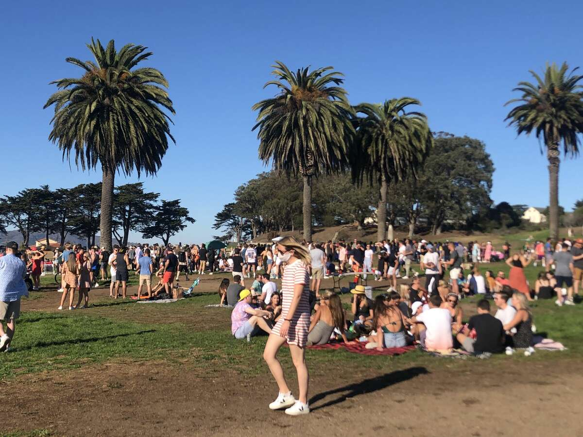 Large groups of people hang out at Fort Mason in San Francisco on Oct. 17, 2020, during a heat wave. The city moved into the yellow tier in California's COVID-19 reopening plan Tuesday.