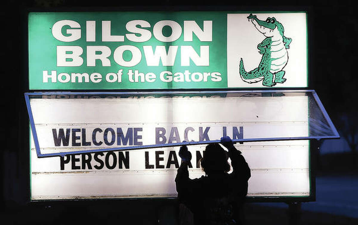 """The sun was barely up Monday as Gilson Brown School custodians were outside changing the sign outside to reflect the start of """"in-person learning."""""""