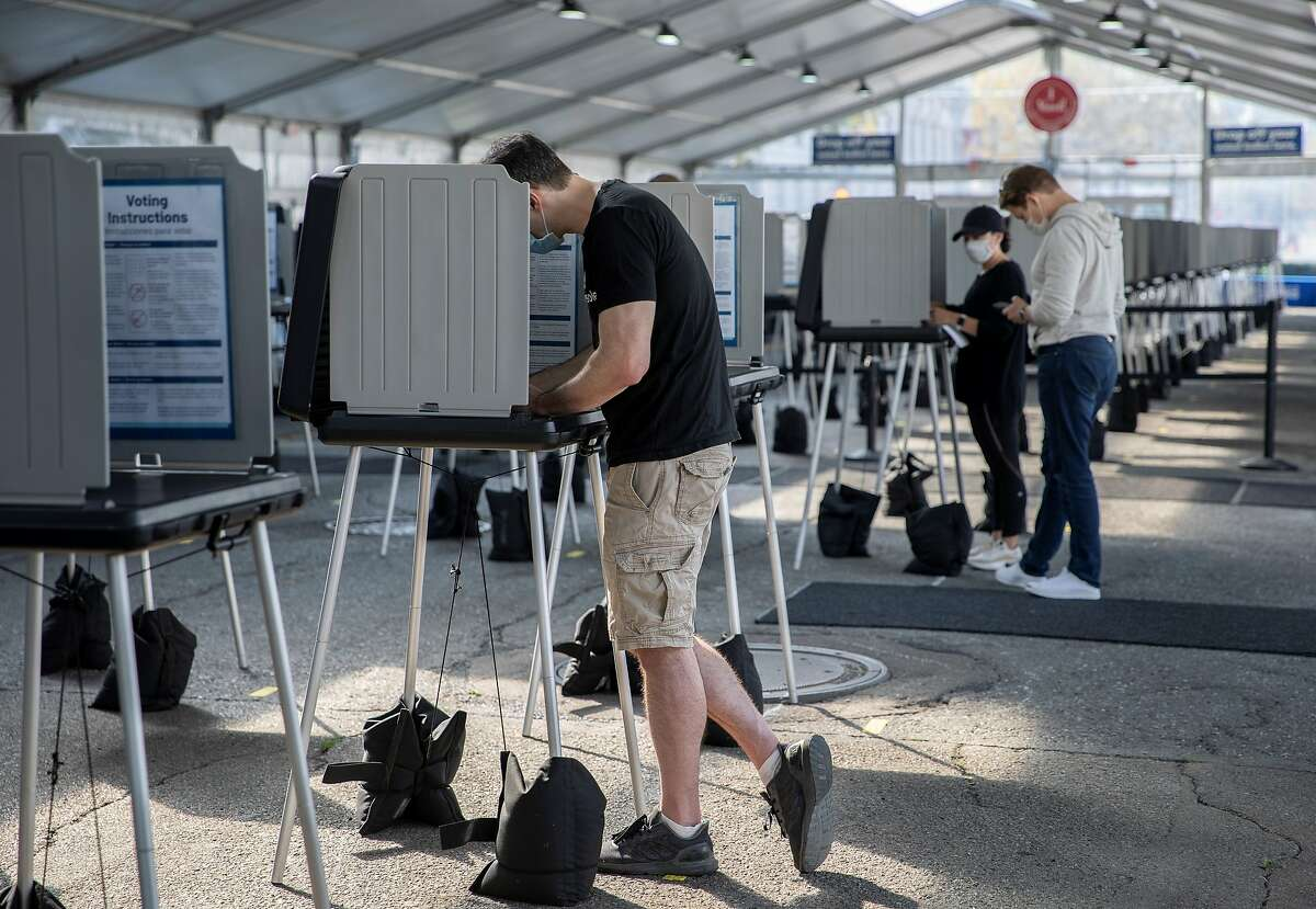 People are seen at an outdoor voting center in San Francisco on Oct. 5, 2020. The city set up an outdoor voting center outside City Hall to provide service for voters during the COVID-19 pandemic.