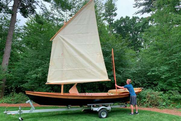 Jacob Hyde of Midland makes an adjustment to his finished sailboat. (Photo provided)
