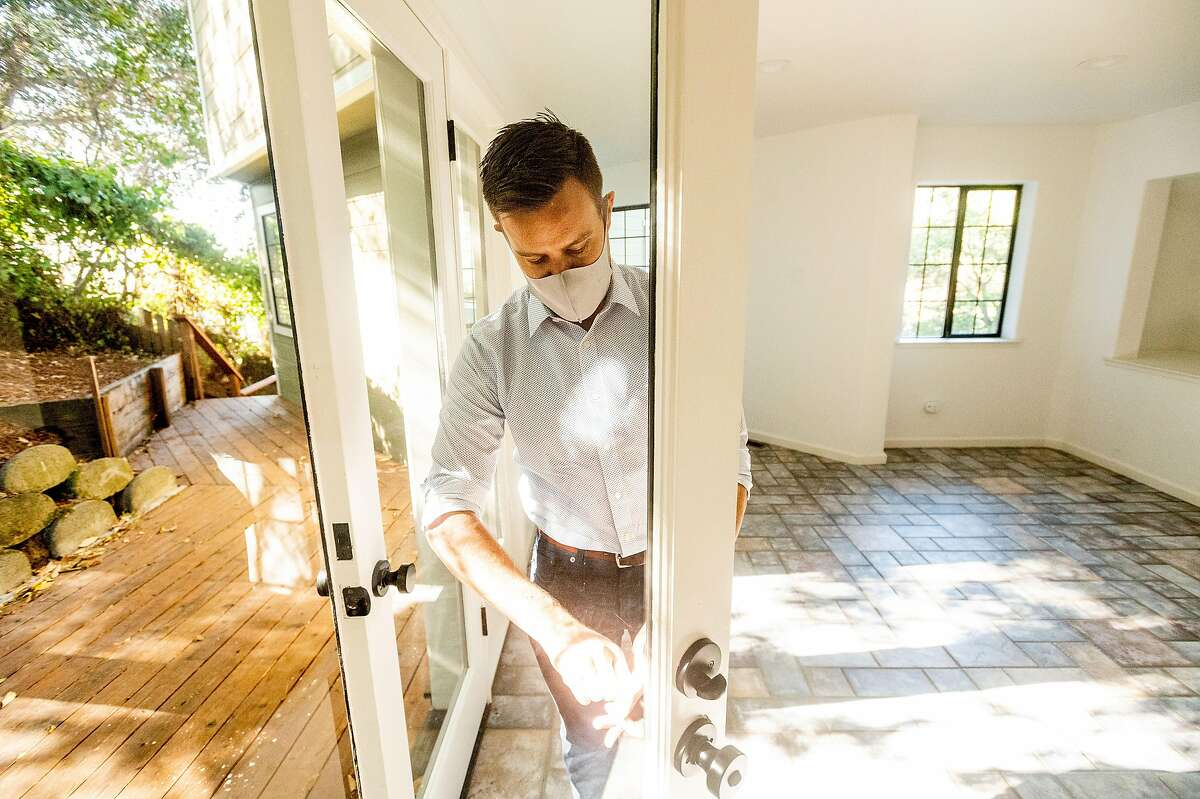 Real estate agent Justin Palmer checks a lock at a home he sold recently in Oakland. Home prices have risen considerably.