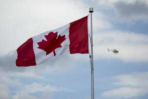 A helicopter flys past a Canadian flag in Niagara Falls, Ontario, Canada, on Wednesday, June 21, 2017. The 150th anniversary of Canada, promoted as Canada 150, marks the sesquicentennial anniversary of the Canadian Confederation and will be celebrated on nationally on July 1, 2017. Photographer: Brent Lewin/Bloomberg ORG XMIT: 700073261