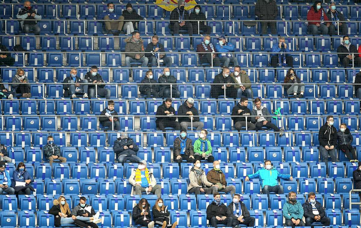 Fans spaced out at Saturday's Bundesliga match between TSG Hoffenheim and Borussia Dortmund in Sinsheim. Soccer may be put on hold again as Germany struggles with the virus.