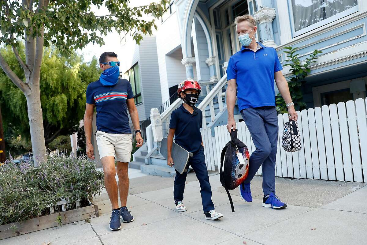 Luis Tamayo (left), David Thompson and their son, Lucas, 9, head home from Adda Clevenger School.
