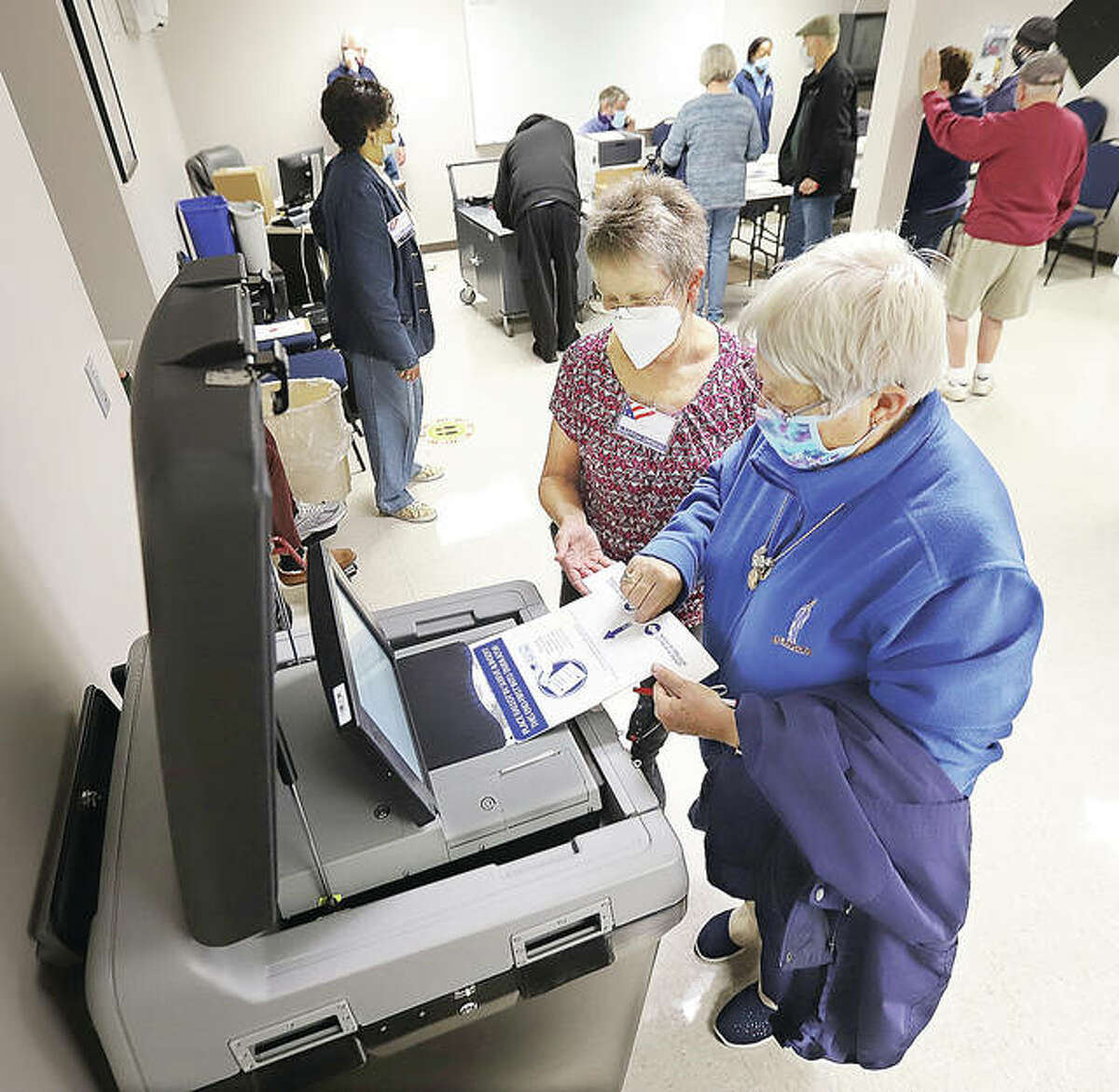 Madison County Election Judge Sharon Cox, working at the Alton early voting site inside the Scott Bibbs Center, helps a voter cast her ballot into the tabulation maching Monday on the first day of expanded voting.