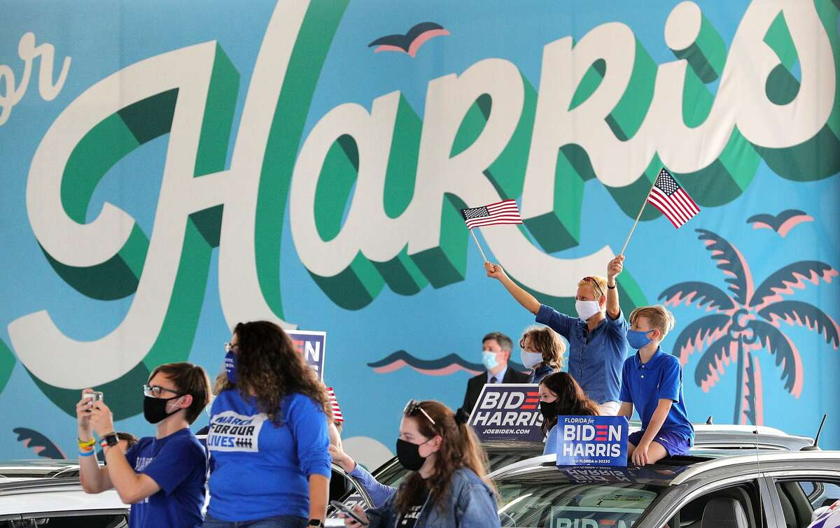 Supporters cheer Democratic vice presidential nominee Sen. Kamala Harris she delivers remarks during an early-voting event at the Central Florida Fairground, Monday, October 19, 2020. Trump supporters demonstrate nearby (background.) (Joe Burbank/Orlando Sentinel/TNS)