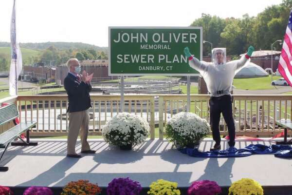 """HBO comedian John Oliver and Danbury Mayor Mark celebrate after the ribbon is cut at the newly named """"John Oliver Memorial Sewer Plant."""""""