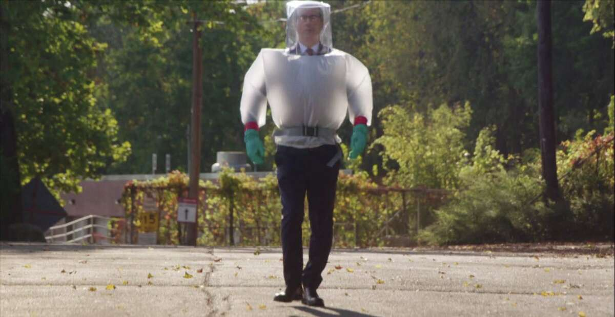 To protect himself from the coronavirus, HBO comedian John Oliver dressed in a plastic suit on his secret visit to Danbury to cut the ribbon on the
