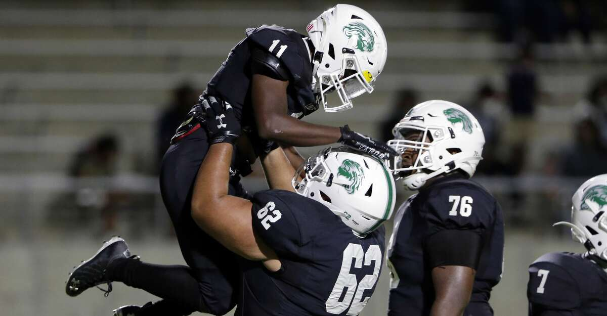 Spring wide receiver Travis Sims Jr. (11) is lifted by guard Kalvin Anaya (62) after Sims' touchdown as Joziah Fogle (76) looks on during the first half of a high school football game Friday, Oct. 9, 2020 at Planet Ford Stadium in Spring, TX.