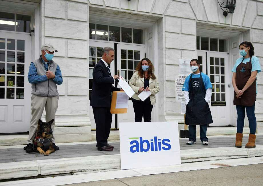 Greenwich First Selectman Fred Camillo presents Abilis President and CEO Amy Montimurro with a declaration marking October National Disability Employment Awareness Month beside the First Selectman's Advisory Committee for People with Disabilities Chairman Alan Gunzburg, left, and Abilis clients Danny Clarke and Dana Verlander outside Town Hall in Greenwich, Conn. Monday, Oct. 19, 2020. First Selectman Camillo acknowledged the work that the nonprofit Abilis is doing to get employment for its special needs clients through programs at the Greenwich Hospital, Greenwich Library, and Coffee for Good cafe. Photo: Tyler Sizemore / Hearst Connecticut Media / Greenwich Time