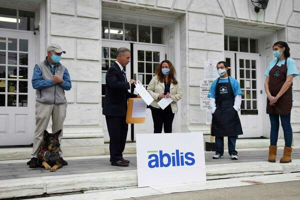 Greenwich First Selectman Fred Camillo presents Abilis President and CEO Amy Montimurro with a declaration marking October National Disability Employment Awareness Month beside the First Selectman's Advisory Committee for People with Disabilities Chairman Alan Gunzburg, left, and Abilis clients Danny Clarke and Dana Verlander outside Town Hall in Greenwich, Conn. Monday, Oct. 19, 2020. First Selectman Camillo acknowledged the work that the nonprofit Abilis is doing to get employment for its special needs clients through programs at the Greenwich Hospital, Greenwich Library, and Coffee for Good cafe.