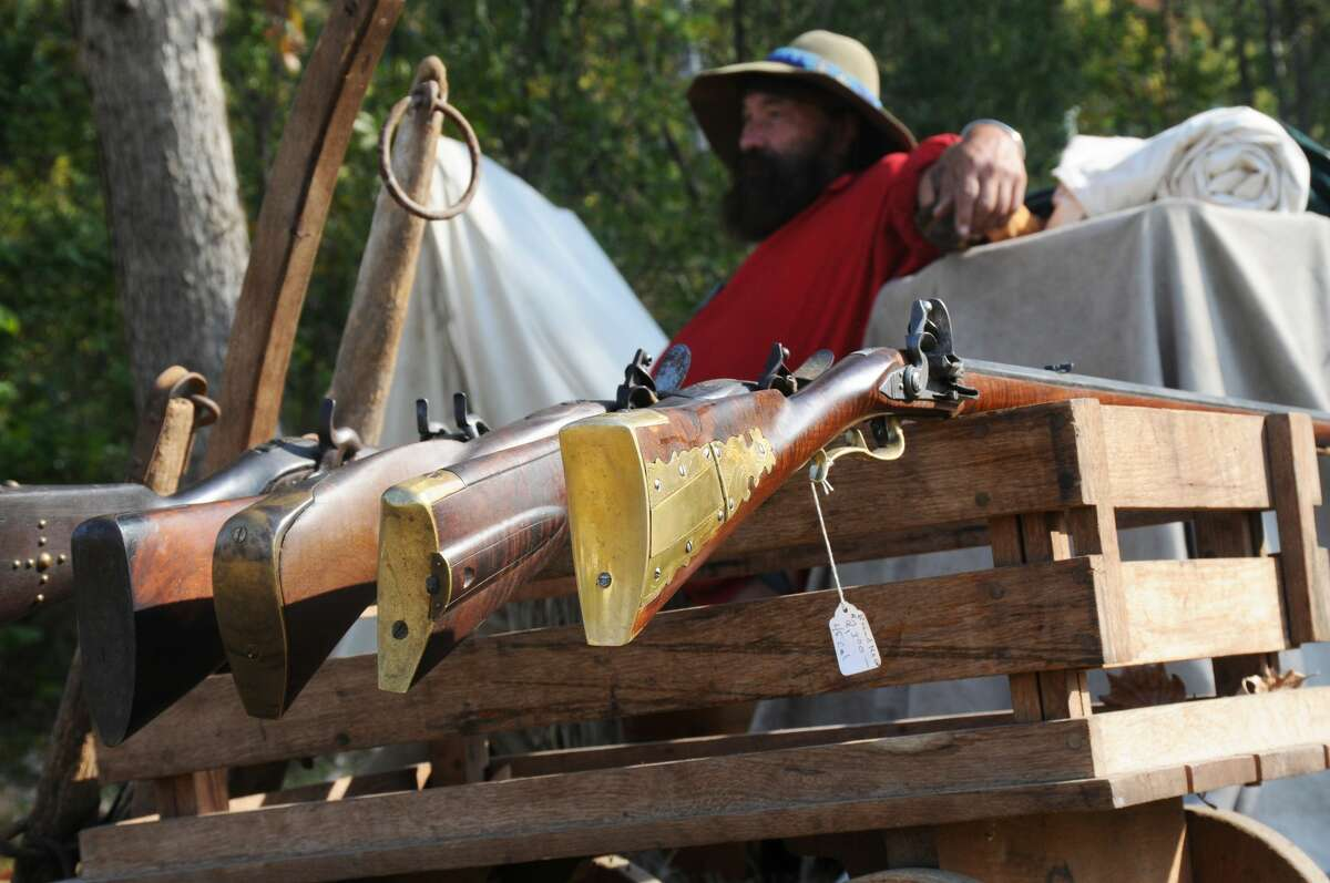A trader sits at his camp with muzzle-loading rifles for show and for sale at the Grafton Rendezvous.