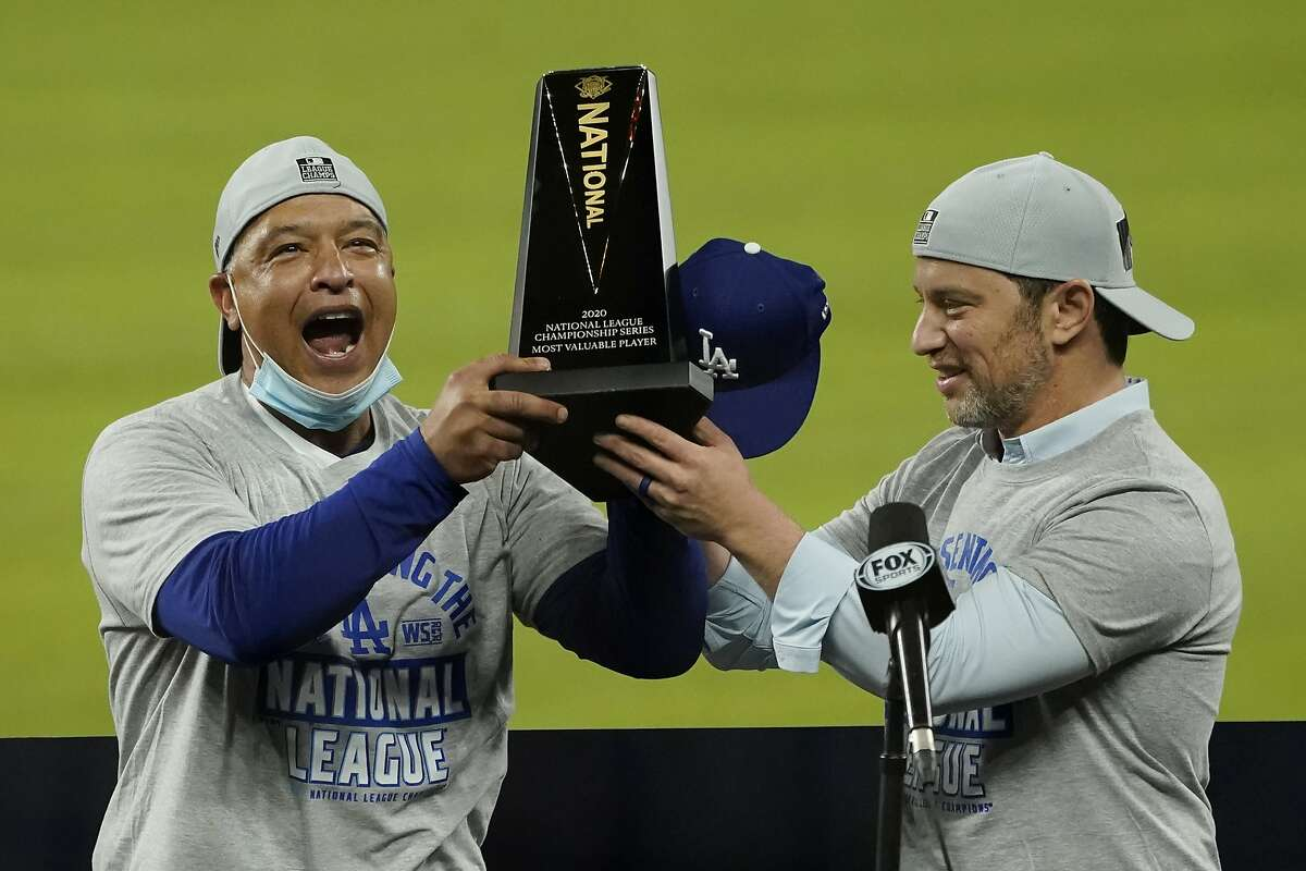 Los Angeles Dodgers manager Dave Roberts, left, and President of Baseball Operations Andrew Friedman celebrate with the trophy after winning Game 7 of a baseball National League Championship Series against the Atlanta Braves Sunday, Oct. 18, 2020, in Arlington, Texas.