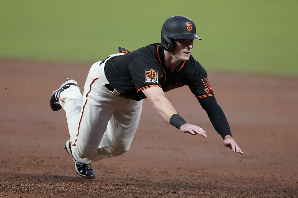 San Francisco Giants' Mike Yastrzemski dives back to first base during the third inning of a baseball game against the San Francisco Giants in San Francisco, Saturday, Sept. 26, 2020. (AP Photo/Eric Risberg)