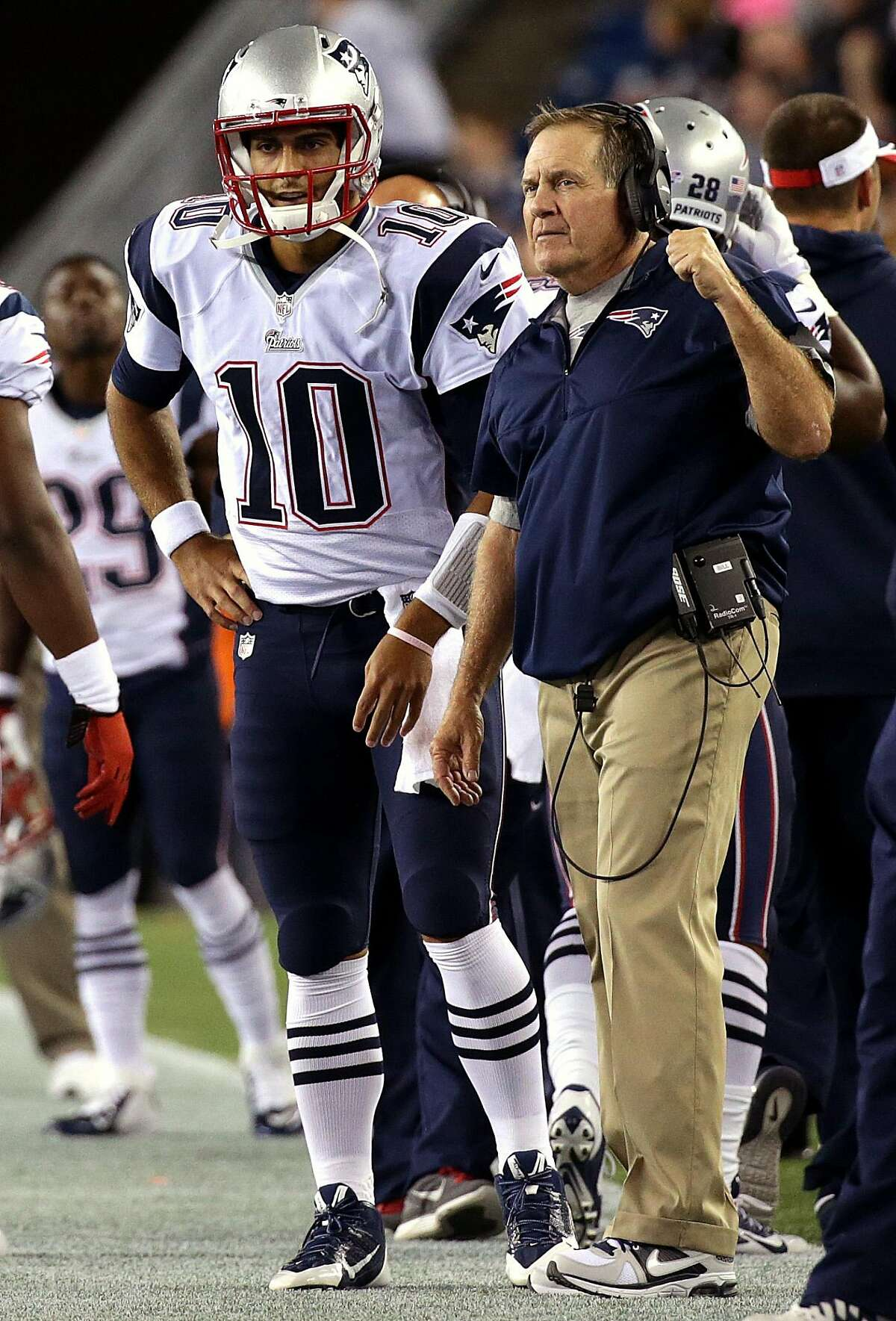 New England Patriots quarterback Jimmy Garoppolo (#10) talks with New England Patriots head coach Bill Belichick on the sidelines.