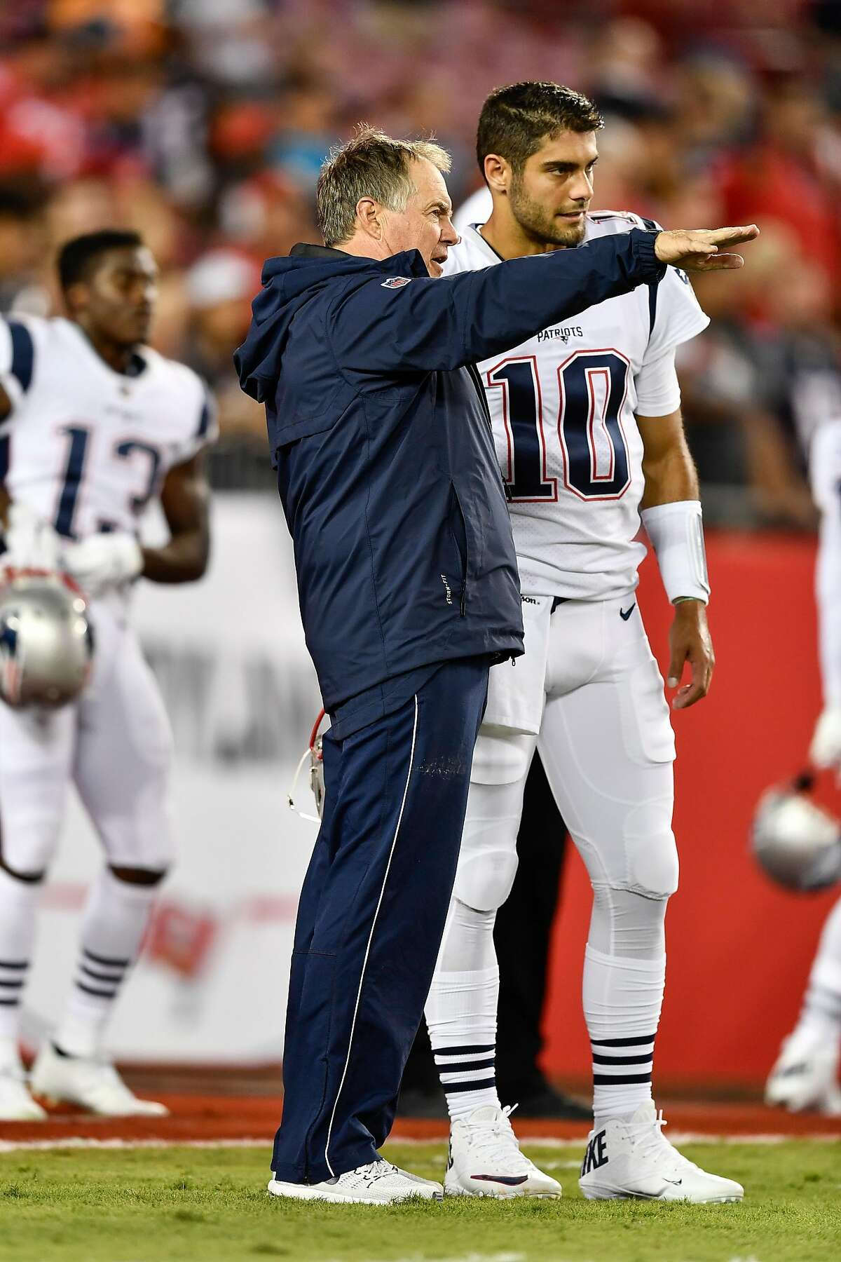 New England Patriots head Bill Belichick speaks to New England Patriots quarterback Jimmy Garoppolo (10) prior to an NFL football game between the New England Patriots and the Tampa Bay Buccaneers on October 05, 2017, at Raymond James Stadium in Tampa, FL. The Patriots defeated the Buccaneers 19-14.