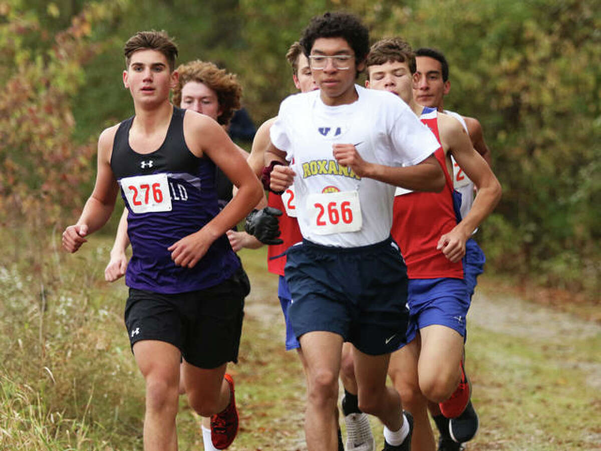 Roxana's Carlos Ruvalcaba (front right) takes Litchfield's Camden Quarton (left) and the lead pack into the back half of the opening mile of the South Central Conference Meet on Monday at Southwestern High School in Piasa. Ruvalcaba won the race to defend his SCC title, with Quarton placing second.
