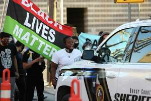 Protesters surround a Bexar County sheriff's vehicle outside the county jail in August during a demonstration against the shooting death of Damien Lamar Daniels by a Bexar County Sheriff's deputy. The CALM approach would not have been used in this incident, officials said, because Daniels was armed.