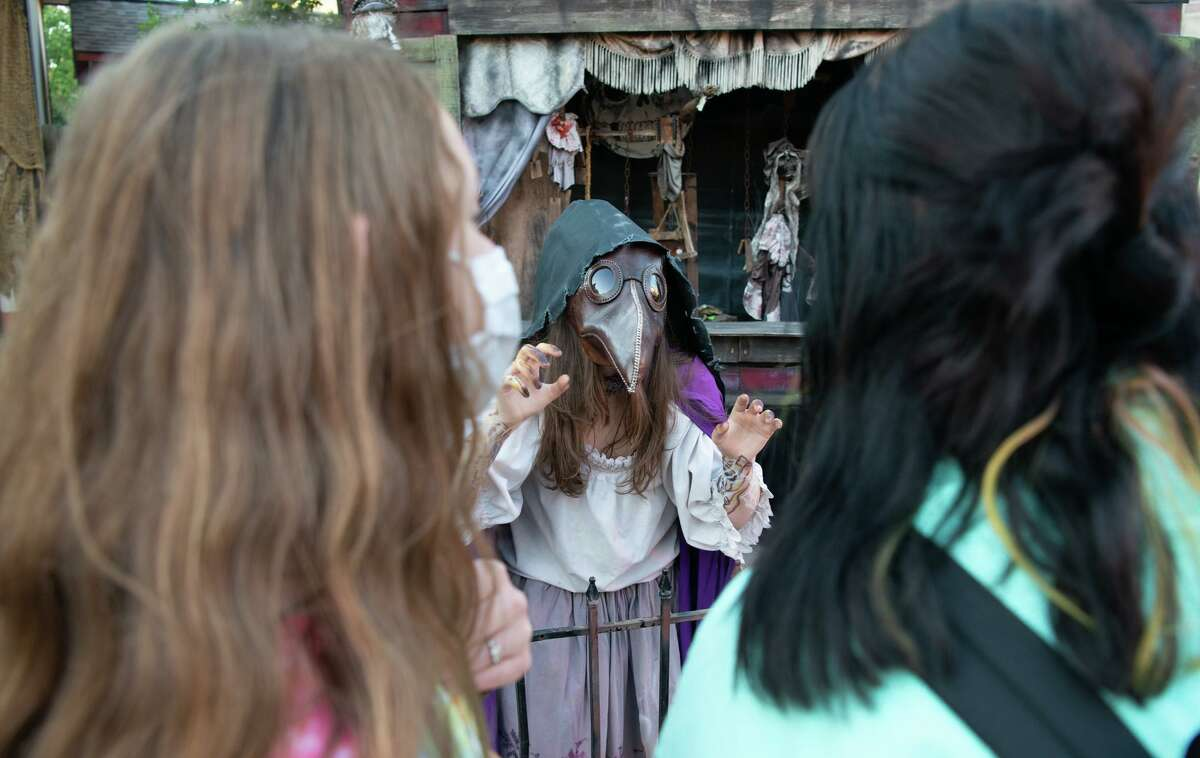 Arianna Bullox and Hailey Roese look at the monsters during Halloween activities at Six Flags Texas. The haunted houses have moved outdoors with social distancing and mask protocals in place.