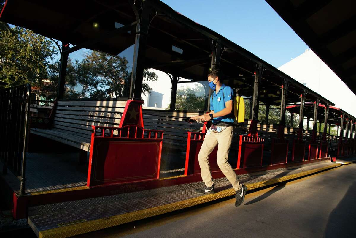 Pablo Vasquez sanitizes the park train during Halloween activities at Six Flags Texas. The haunted houses have moved outdoors with social distancing and mask protocals in place.